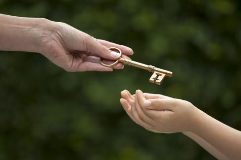 Ręka przekazująca klucz drugiej osobie jako metafora wydziedziczenia