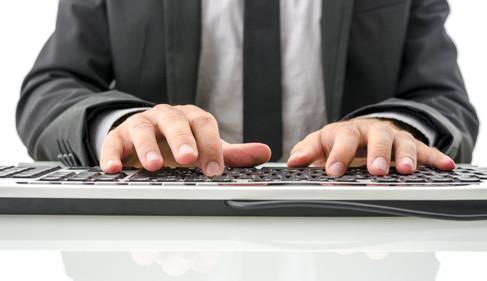 człowiek piszący na komputerze jako metafora windykacji elektronicznej
