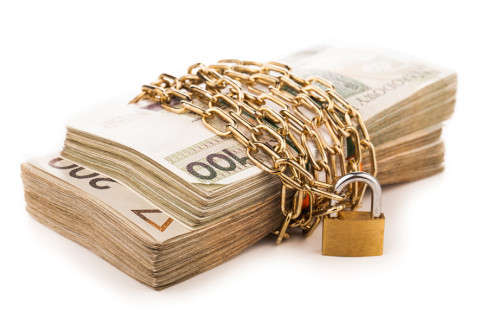 Plik pieniędzy obwiązany łańcuchem i zapięty na kłódkę