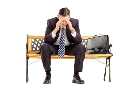 Upadłość likwidacyjna - załamany biznesmen siedzący na ławce