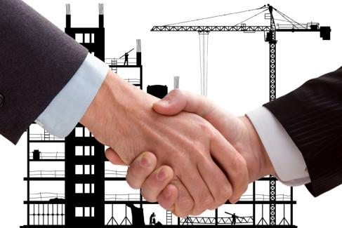 Wspólnicy podają sobie rękę na tle budowy