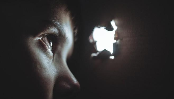 Dziecko patrzące przez dziurę jako metafora uprowadzenia dziecka